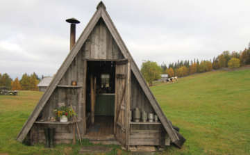 triangle wooden hut for cheese making in green field