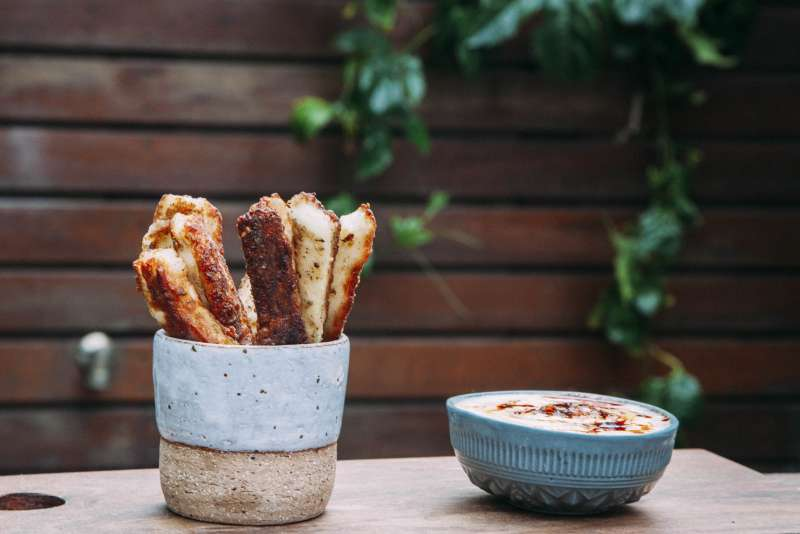 Aphrodite Halloumi Fries in bowl and garden