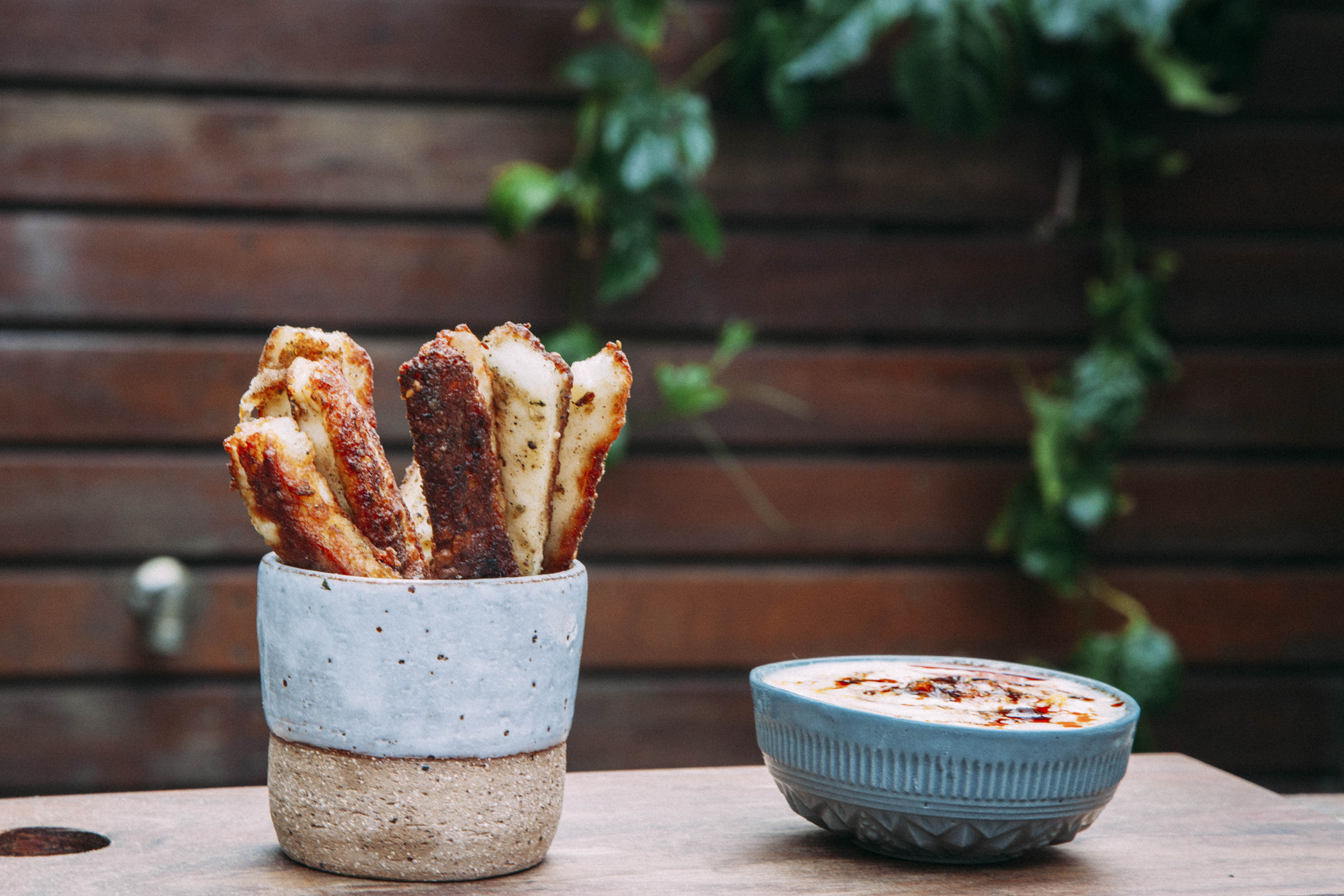 Aphrodite Halloumi Fries in bowl and garden